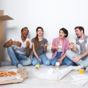 Buying a property with friends, friends sharing pizza moving into new home